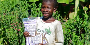 "a boy holding "" Impact Lives"" Bags full of food"