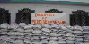 "in fornt pf Mercy and Grace Building, a sign above dozens of bags of food says, "" Donated by Feeding The Nations"""
