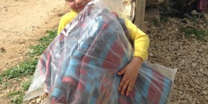 little girl caring bag of blankets