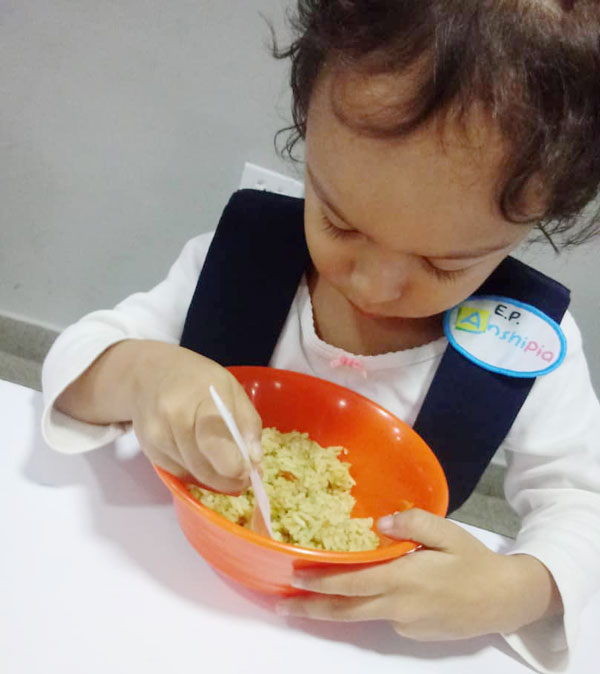little girl eats from rice bowl