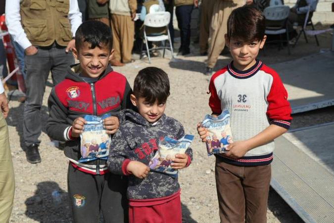 Three boys with food packets