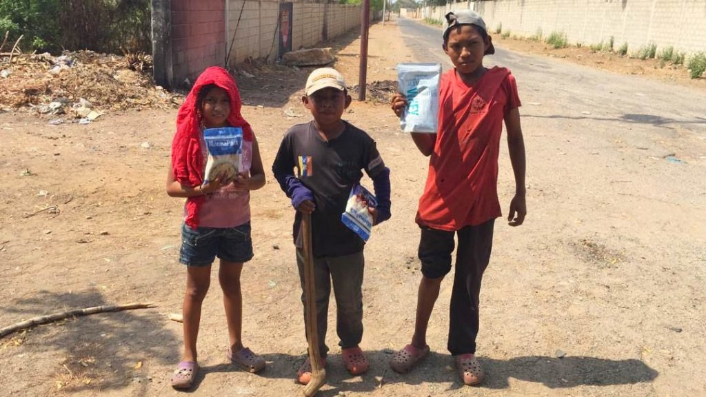 Three Venezuelan children carry manna packs home to provide much-needed meals.